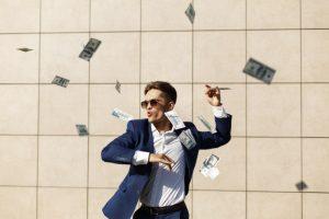 młody mężczyzna rozrzuca pieniądze